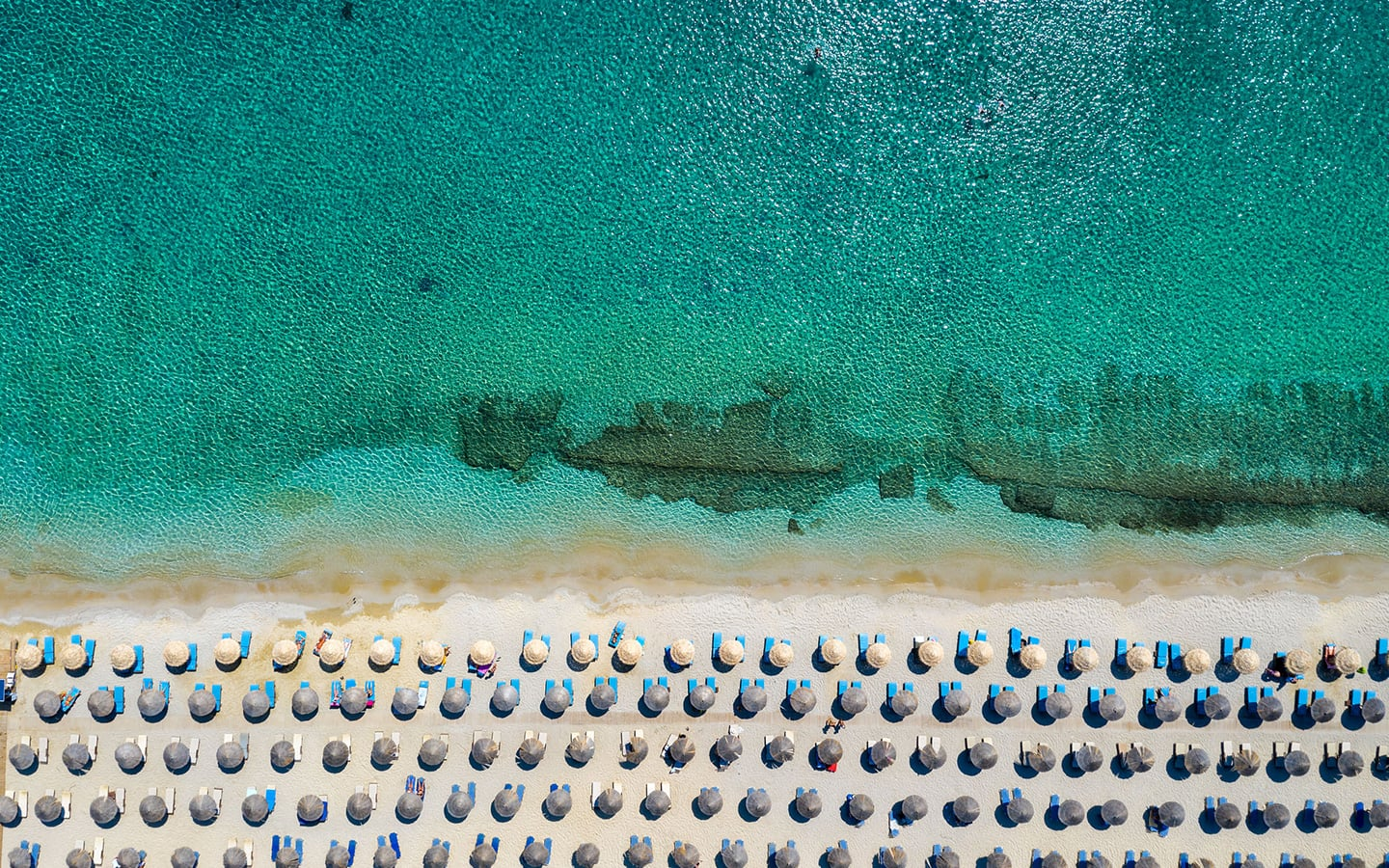 Overhead view of a beach in Mykonos. Sun umbrellas on the beach and crystal clear sea.