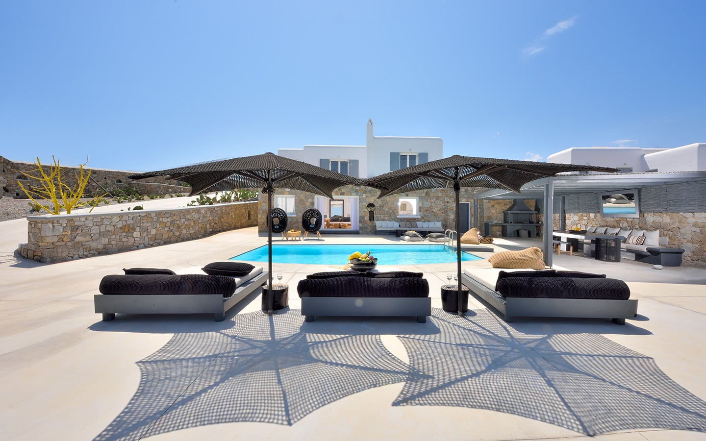 Comfortable beds and umbrella by the pool in a Mykonos Best luxury villa.