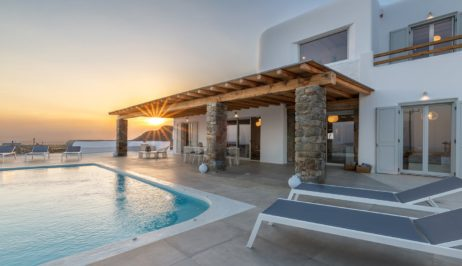 Sunset in Villa Meli. Sun loungers by the pool and the exterior of the luxury villa.