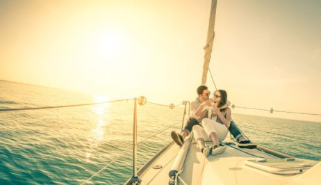Romantic couple on a Mykonos Best luxury yacht sailing in the middle of the Aegean sea.