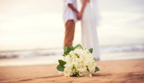 A newly wed couple by the sea in Mykonos and a wedding bouquet with white flowers.