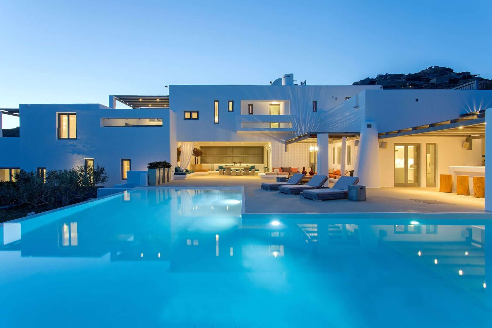 Crystal clear swimming pool in Villa Armonia in Mykonos and view of the villa's exterior.
