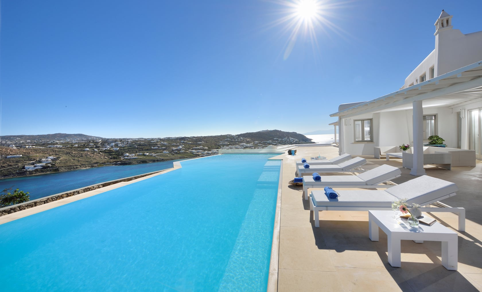 Sun loungers by the swimming pool in Villa Divine overlooking the sea and a village.