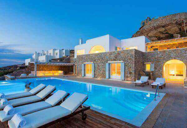 Dusk at a Mykonos Best luxury villa. Sun loungers by the pool and the exterior of the villa.